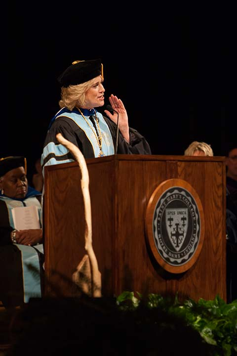 Sister Madeleva's favorite walking stick next to the podium as President Cervelli speaks at her inauguration