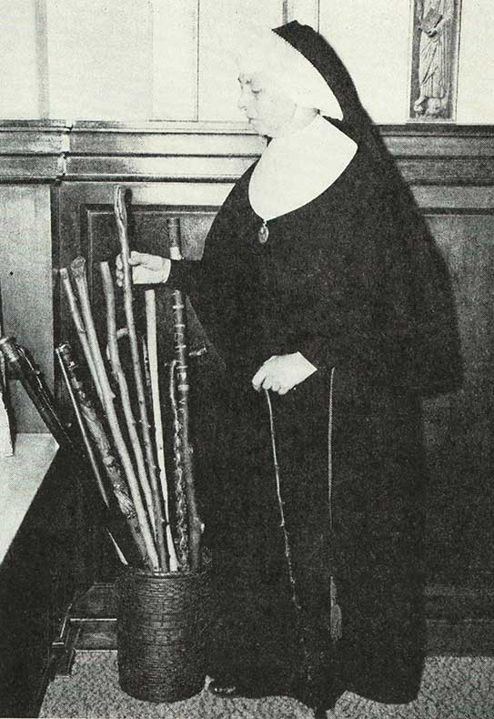 Sister Madeleva holding a walking stick standing next to a container with more of her walking stick collection