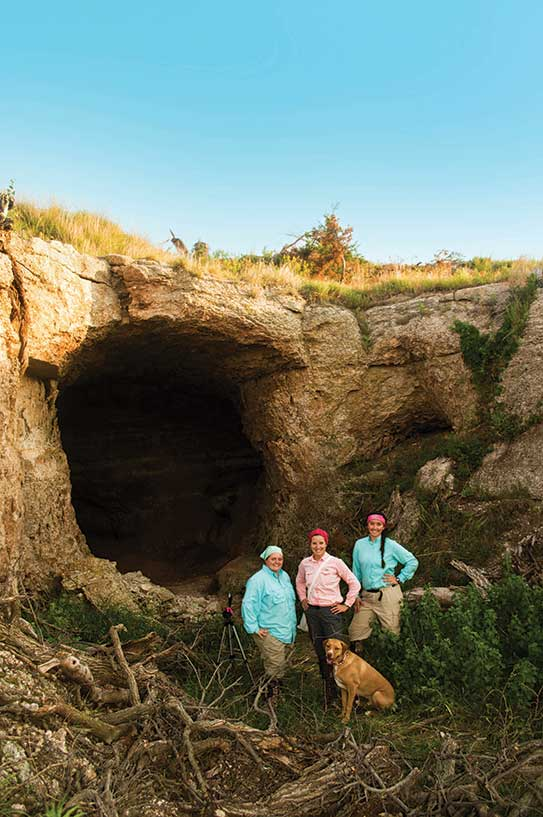 Cassi Mardis '17, professor Laura Kloepper, her dog, Kaipo, and Stephanie Dresseen '17 outside of a cave in Atena, KS.