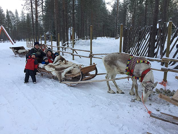 The Newcamp family in snowy Finland, riding in a sleigh pulled by reindeer