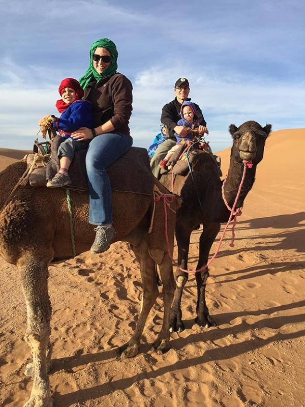 The Newcamp Family rides on Camels with the dunes of Morocco in the background
