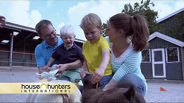 The Newcamp family feeding goats at a petting zoo as seen on House Hunters International