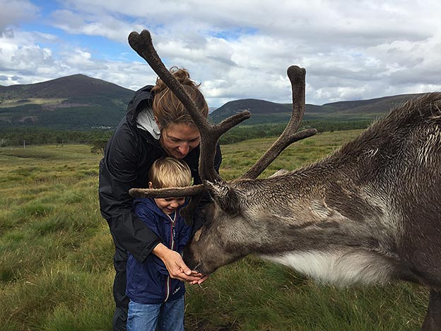 Elizabeth Newcamp and one of her sons feeding reindeer in Scotland
