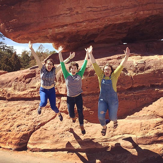 Choir students jumping from red rock formation in Colorado