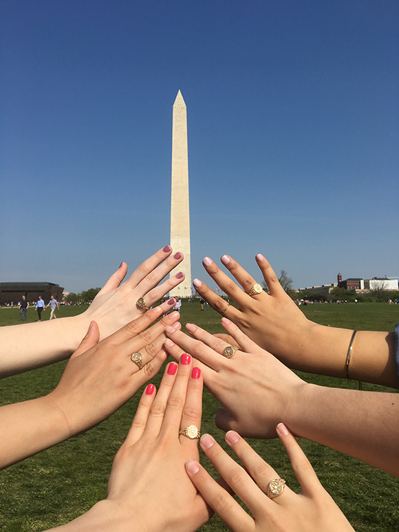 Belles display their rings against backdrop of the Washington Monument