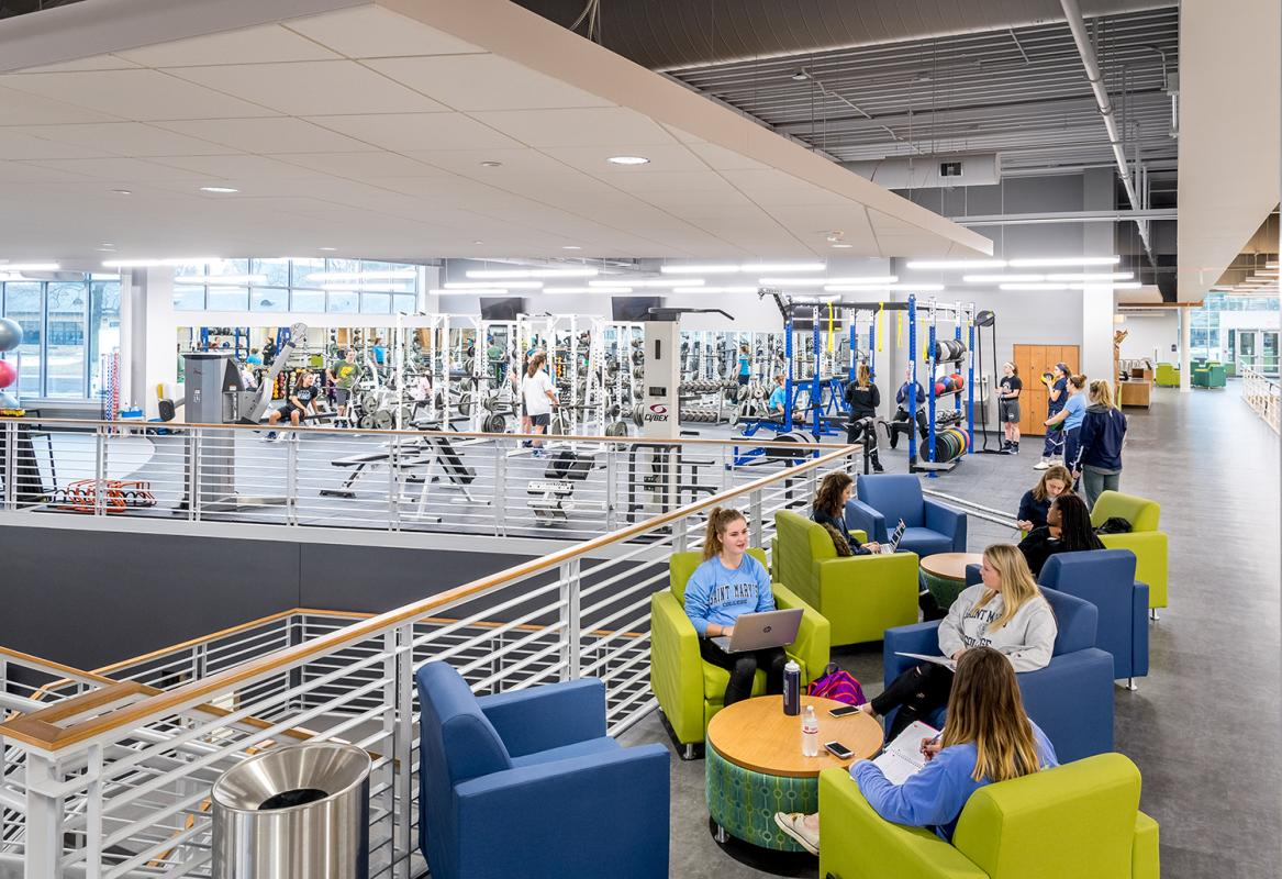 View of main level with a lounge in the foreground and weight training area in the background.