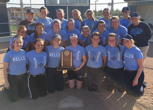 Softball team posing with trophy at softball field