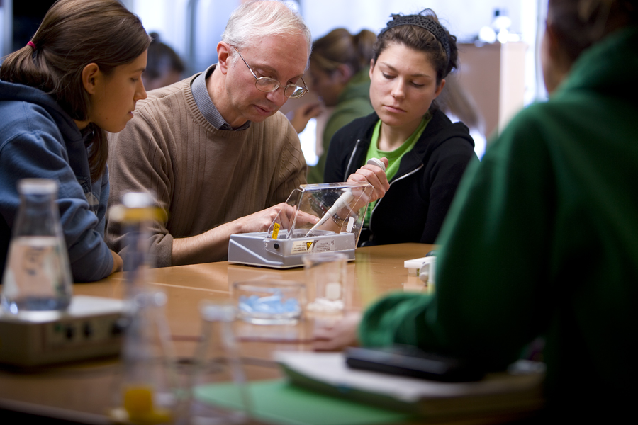 Biology professor Thomas Fogle and students work together on a project.