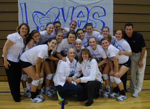 The volleyball team and athletic director Julie Schroeder-Biek pose with Anne Blair Payne '02 before the match.