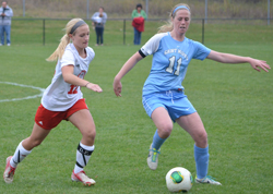 Mary Kate Hussey plays the ball away from Olivet's Lauren Vanderhoff. (photo credit: Rebeka Wiersma)