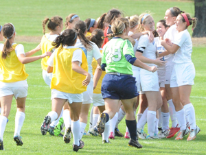 The soccer team rushes onto the field to celebrate Jordan Diffenderfer's (third from right) game-winning goal in overtime.