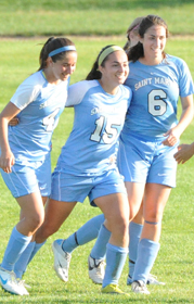 Kelly Wilson, Erin Mishu, and Jordan Diffenderfer celebrate Mishu's goal against Adrian.