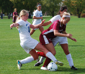 Kari McClowry and Abby Garcia battle with a Calvin player for possession of the ball.
