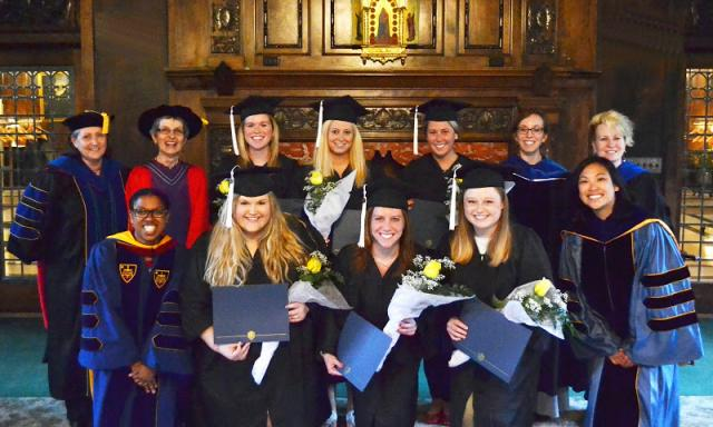 2014 graduates who minored in gender and women's studies pose with faculty.