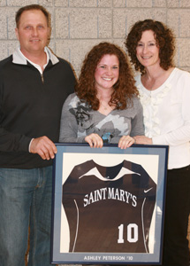 Ashley Peterson with parents Bruce and Chris after having her jersey retired.