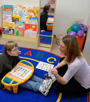 A Saint Mary's College communicative disorders student works with a child in a lab.