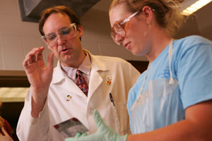 Christopher Dunlap, associate professor of chmistry, works with a student in the lab.