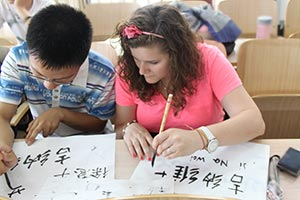While in China, Genevieve's pen pal, X, teaches her to write her name in Mandarin.