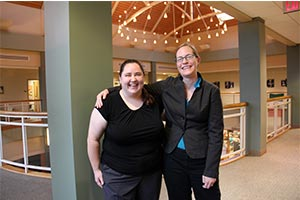 Gina Deom '13 and Kristin Kuter, professor of mathematics share a laugh inside the Student Center.