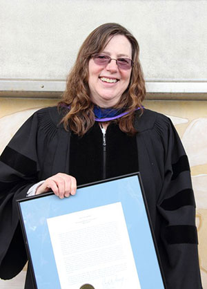 Professor Julie Storme poses with the Spes Unica Award, which she received at Honors Convocation.