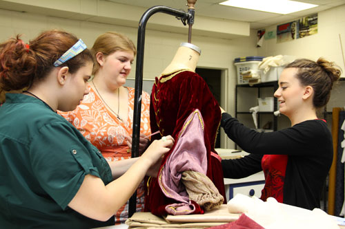 Students work on details of a Madrigal Dinners costume.