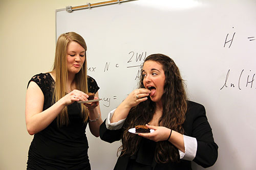 Olivia McIntee '13, left, and Samantha Brown '13, enjoy a brownie and a laugh. Their math problem was to figure out the ideal shape of a brownie pan so the edges aren't burnt. Their answer: a hexagonal pan!