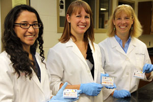 Saint Mary's College chemistry professor Toni Barstis, far right, and from left, Saint Mary's College student researcher Diana Vega Pantoja and SMC alumna researcher Elizabeth Bajema hold the paper analytical device they helped develop at Saint Mary's in