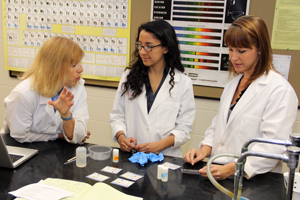 Dr. Toni Barstis, Diana Vega Pantoja '13, and Elizabeth Bajema '11 discuss their paper analytical devices.