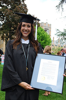 Samantha Grady '15, donning the Lumen Christi medal given to her at Commencement, holds the citation read at the graduation ceremony.