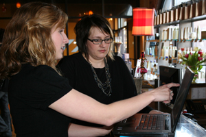 Alumna Kathleen Mills '10, left, consults with Sonia Stancombe, owner of Nicholas J Salon and Spa in South Bend. Kathleen recently made a breakthrough for the business when she figured out how to get the business's sales program to communicate with the ac