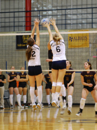 players blocking a volleyball over the net