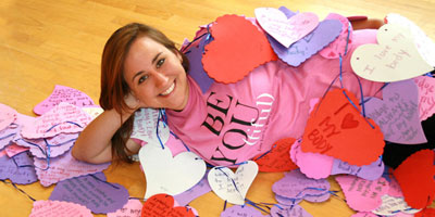 "Laura Glaub '12, creator of ""Love Your Body Week"" poses in a ""Be-You-tiful"" t-shirt."