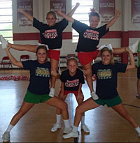 Katie, bottom left, and her sister, Sarah, bottom right, help younger students with cheerleading.