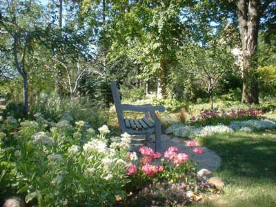 bench with pink and white tulips beside it