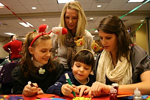 Brittney Sego, 12, and her brother, Andy, 6, make crafts with nursing juniors Kari Keller, standing, and Elizabeth Mueller at a Pediatric Respite Program Christmas party held at the College in December 2011.