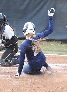 Jamie Young slides into home for the game-winning run in game one at Adrian.