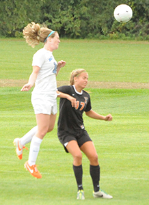 Mary Kate Hussey heads the ball past a defender on its way in for the Belles' goal.