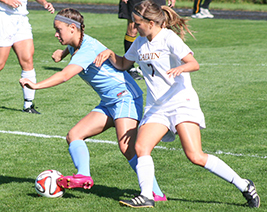 Jenn Jarmy (left) keeps possession of the ball against Calvin. (photo courtesy of Jeff Febus, Calvin SID)