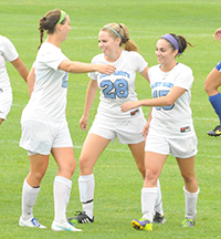 Erin Mishu (right) celebrates her goal with Kathryn Lueking and Kerry Green.