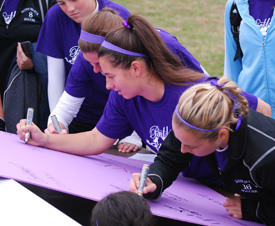 Team members sign the empowerment wall prior to the Domestic Violence Awareness Month soccer game in October.