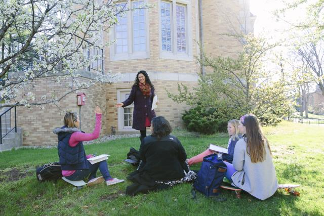 professor calling on student with her hand raised during class outdoors