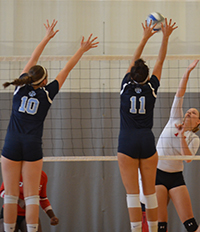 A pair of Belles volleyball players jump to try to block the ball.