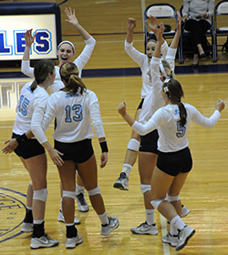 The Belles celebrate a point in the second set against Kalamazoo.