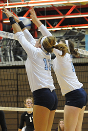 athletes blocking over the volleyball net