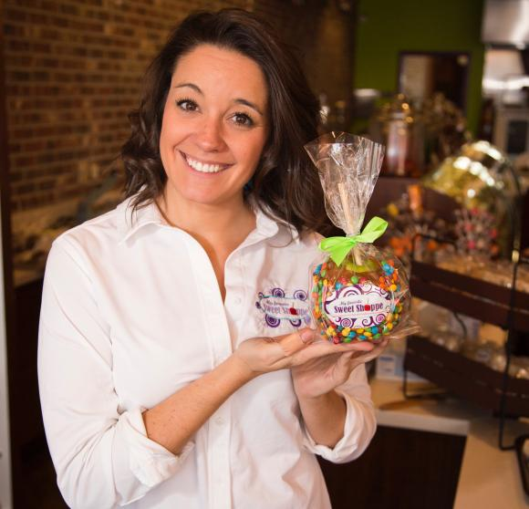 Nina Midgley '11 holds a basket of sweets in her shop in Pittsburgh.