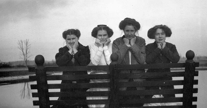 1915 Four students posed on a bench facing the camera by Lake Marian