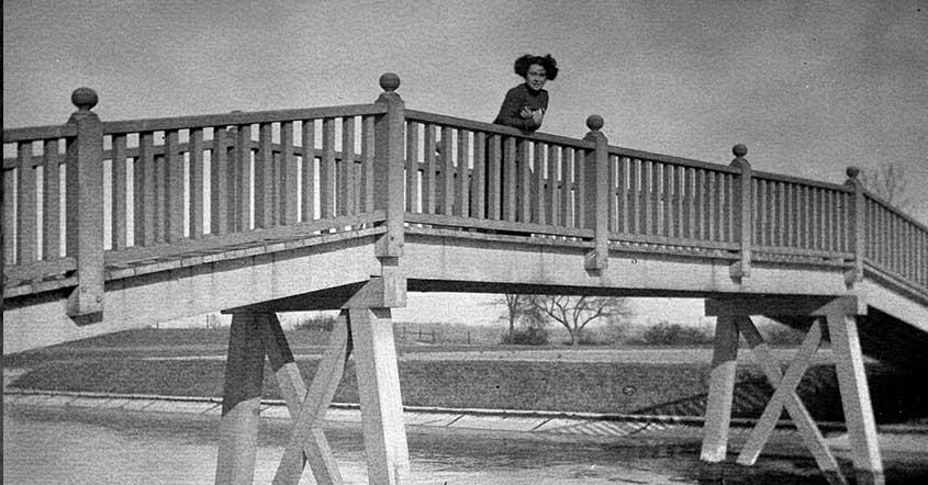 1915 Student leaning over railing on bridge over Lake Marian, sparse trees in background