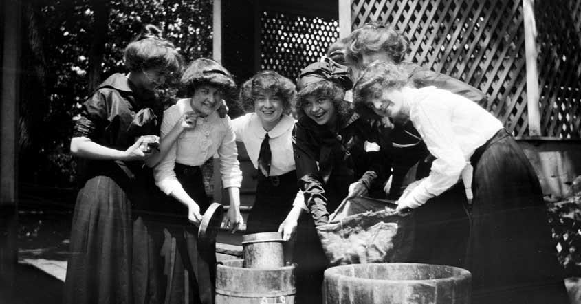 1915 smiling group of students gathering by old barrels