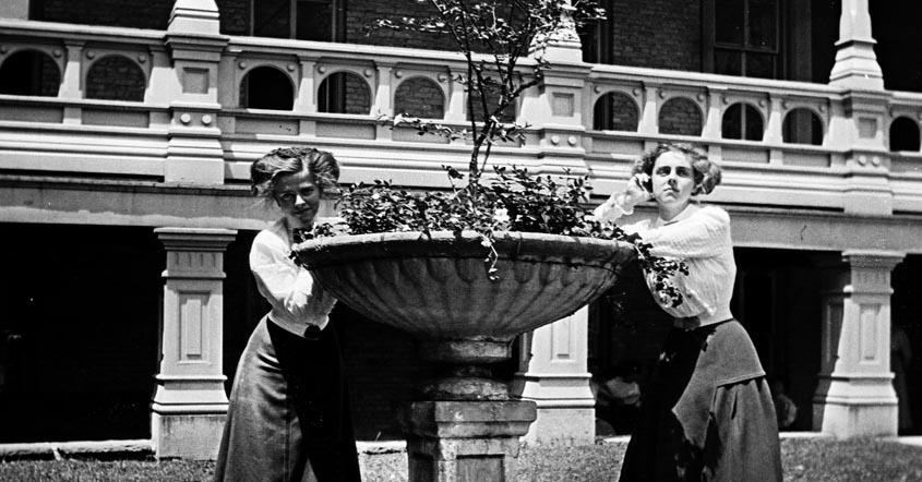 1915 image of two girls posing by flower planter in front of hall