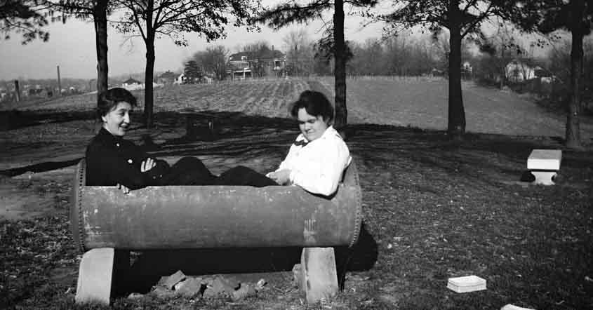 1915 Two students sitting in trough out in a field
